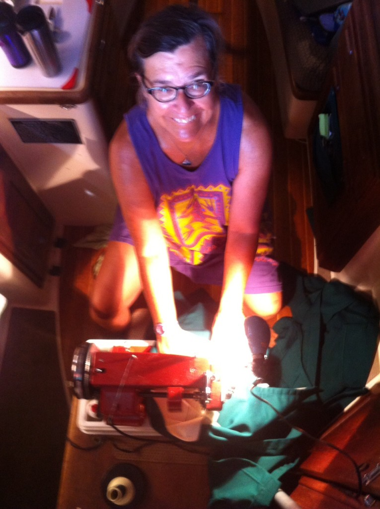 Cindy sewing on a borrowed Sailrite sewing machine on a the landing of the companionway.