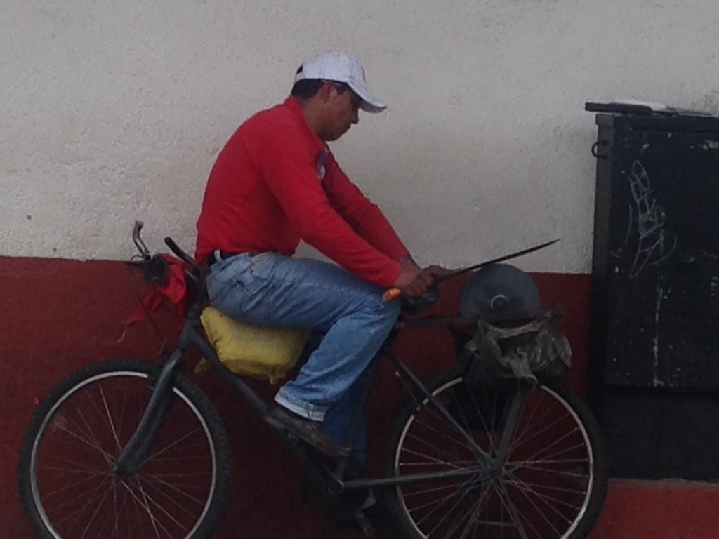 A vision of old Mexico - a knife sharpener on the sidewalk near the  main square, awaiting his next customer