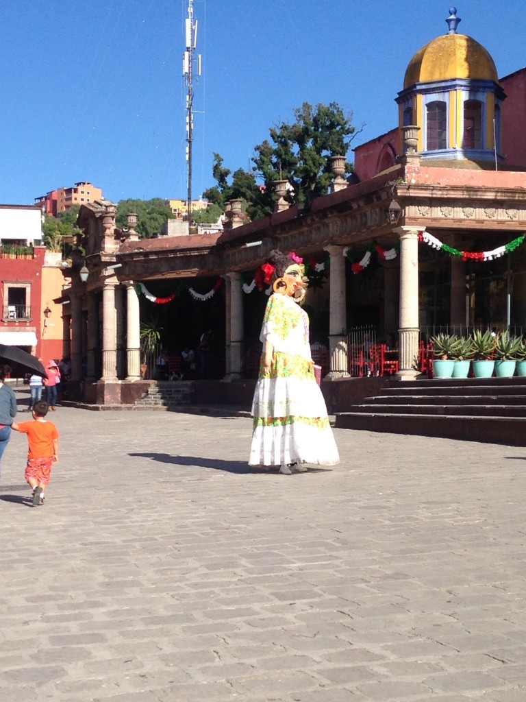 An oversized costumed person on stilts roams the San Miguel Zocolo, playing with children and looking pretty, lending a magical and festive aire to this Pueblo Mágico.