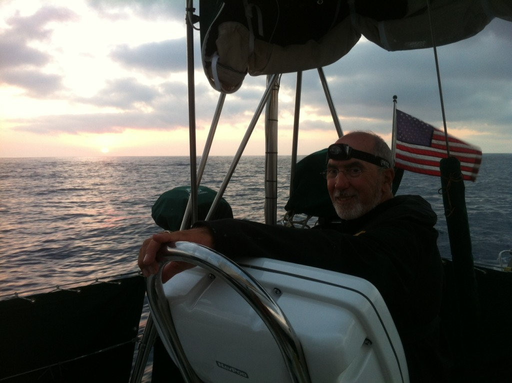 Rick at sunset, preparing for a night at sea, with his headlight mounted on his forehead.  We always have a little toast at sunset - this time a shot of the captain's rum